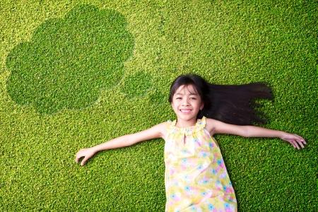 niños felices: Niña asiática que descansa sobre la hierba verde Foto de archivo