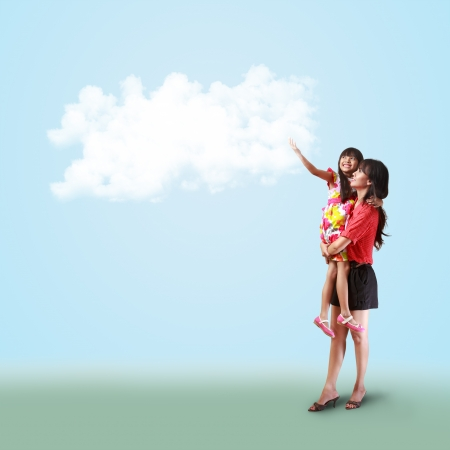 Mother holding her little daughter and catch something on the cloud photo