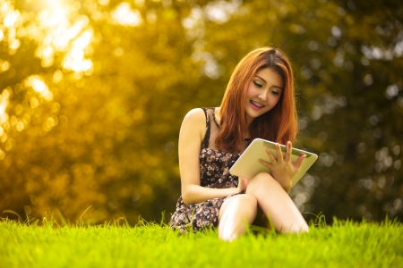 Asian woman using digital tablet in park, Outdoor Portrait photo