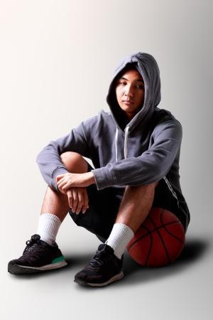 Sad teenager boy sitting on basketball, Sad on face  photo