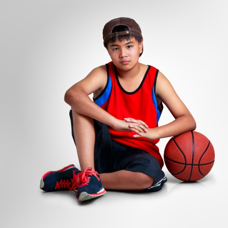 kid  playing: Teenager boy sitting with basketball