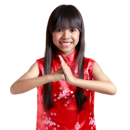 respecting: Smiling little asian girl with cheongsam respecting on chinese new year festival, Isolated over white background Stock Photo