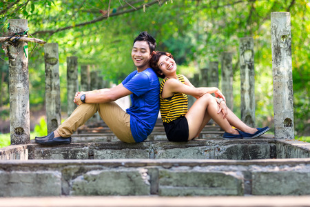 Happy young asian couple relaxed in the park back to back photo