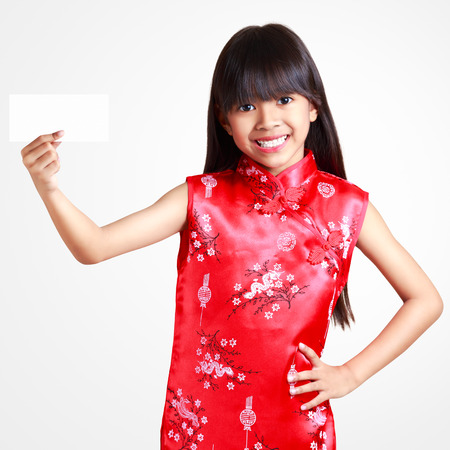 Smiling little asian girl with cheongsam respecting holding empty paper in herhand photo