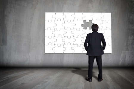 puzzle shadow: Businessman figuring out puzzle pieces with piece missing on grey wall