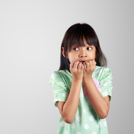 Scared little girl hiding face on grey background with clipping path photo