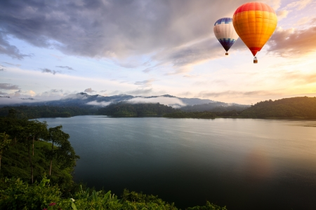 Hot air balloons floating over lake Stock Photo