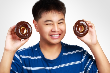 childhood obesity: Little asian boy holding a chocolate donuts, Isolated on white background