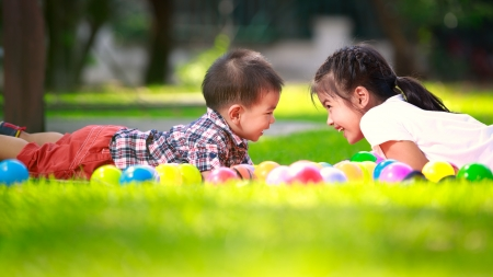 Two children, big syster and her young brother are laying on green grass and smile photo