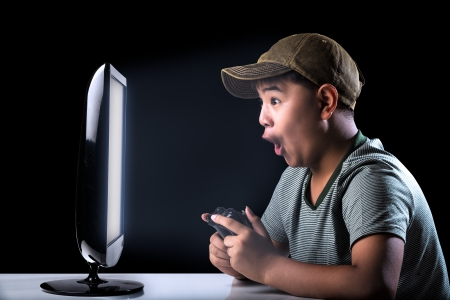 Asian boy excited with computer game with expressing face photo