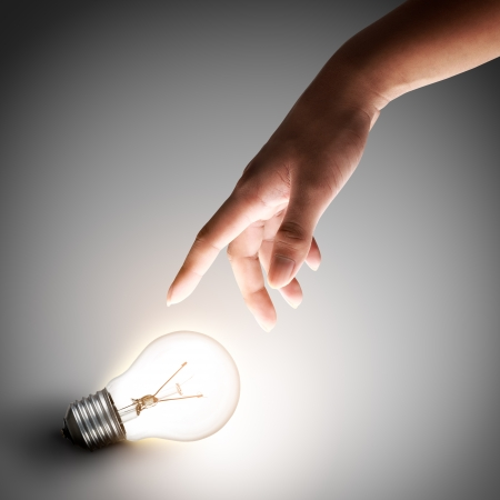 Light bulb with hand on grey background photo