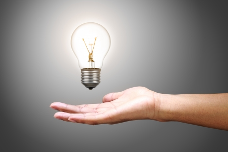 Light bulb in hand, Isolated on grey background photo