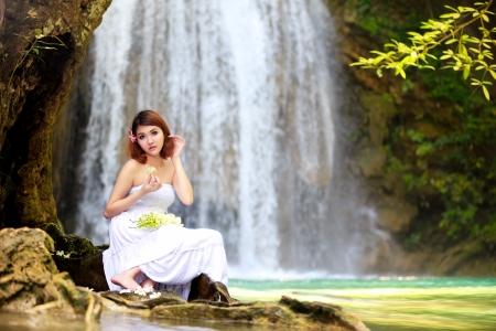 Young woman relaxing in water stream near waterfall photo
