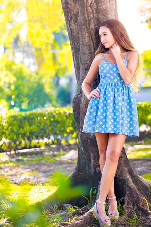Beautiful young woman in park standing under the tree photo