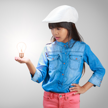 Little asian girl with a light bulb in hand photo