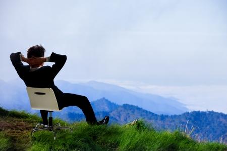 Hombre de negocios joven que se sienta en una silla en la parte superior de la montaña y se ve en el cielo Foto de archivo - 23727852