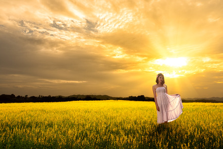 Young asian woman standing in meadows with sunset photo