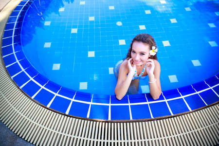 Young woman standing in a swimming pool photo