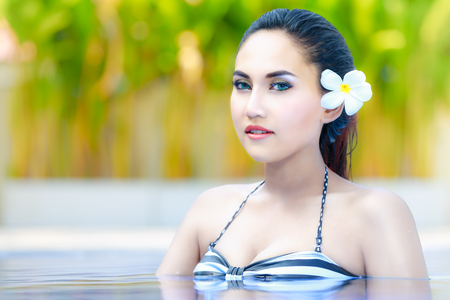 Beautiful young girl relaxing on the swimming pool photo