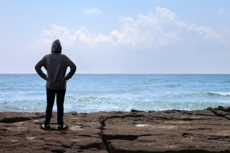 Teenager boy standing on the rock and looking to the sea photo