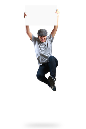 Teenager boy jumping and holding blank paper, Isolated over white photo