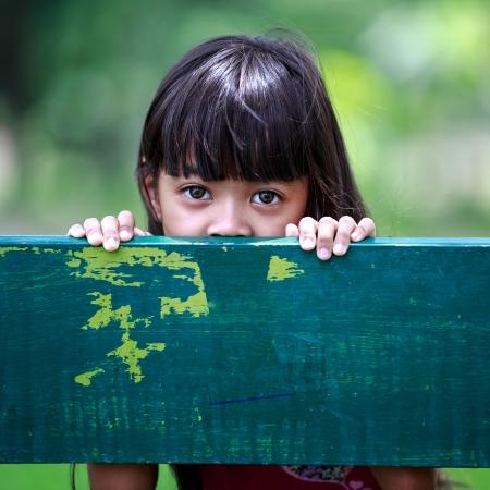petite fille triste: Petite fille triste est assis sur un banc au parc Banque d'images