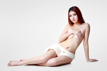 Asian woman wearing towel sitting on the floor, Isolated over grey color photo