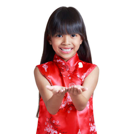 respecting: Smiling little asian girl with cheongsam respecting hands up show something, Isolated over white