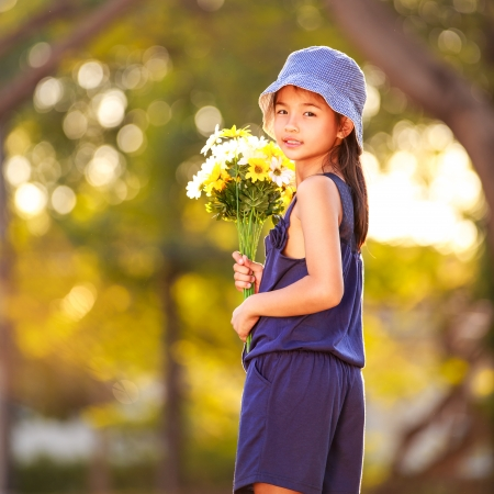 Little asian girl holding a bunch of flowers, Nature background photo