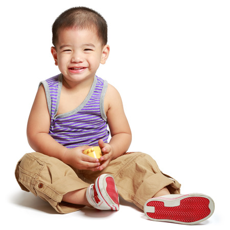 Smiling little asian boy sitting on floor, Isolated over white photo