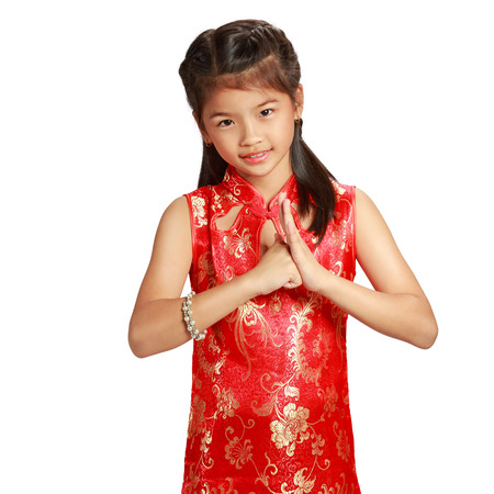 Smiling little asian girl with cheongsam respecting on chinese new year festival, Isolated over white background photo