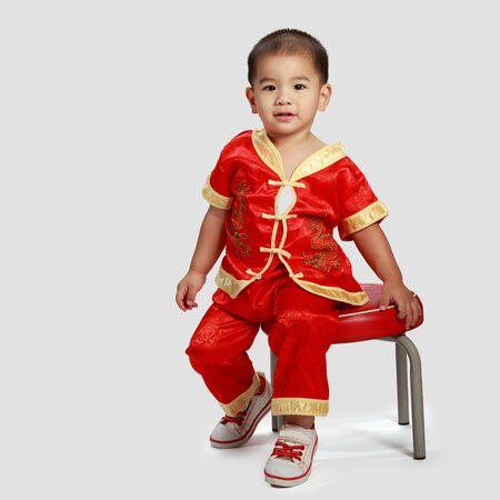 Little asian boy in traditional chinese cheongsam, Isolated on grey background photo