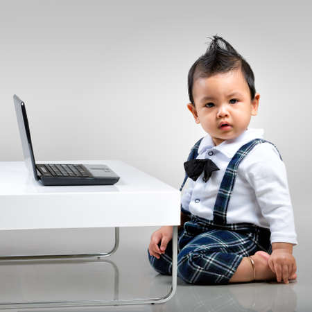 Serious baby boy with laptop photo