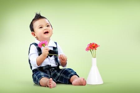 Cute little boy with beautiful flower sitting on floor photo