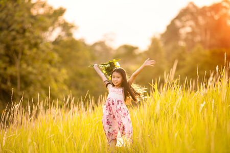 Happy young girl holding flowers and standing on countryside meadow with raised hands photo