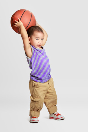 Little boy with basketball, Isolated over grey background photo