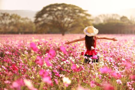 아시아 소녀 코스모스 꽃 필드에 서있는 그녀의 팔을 엽니 다