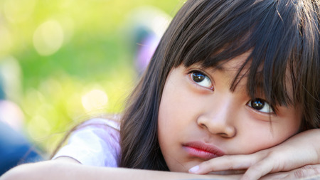 Closeup thinking liitle asian girl, Outdoor portrait photo