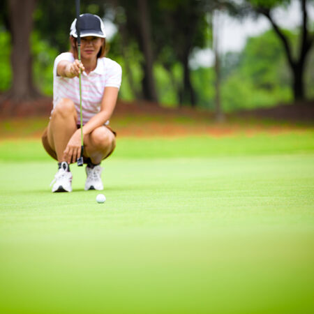 Female golf player with putter squatting to analyze the green at golf course, Select focus at golf ball photo