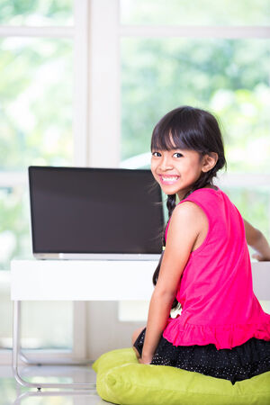 Little asian girl with a laptop computer at home photo
