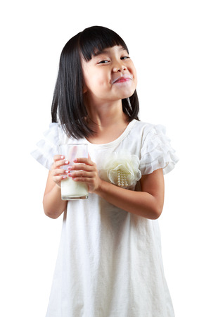 Happy little asian girl holding a cup of milk, Isolated over white