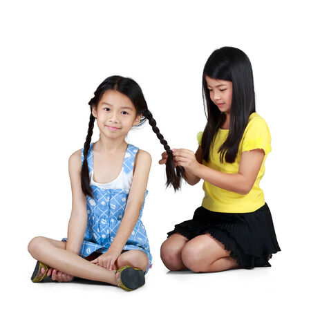 braiding: Girl braiding hair to other girl to look  cute  Stock Photo