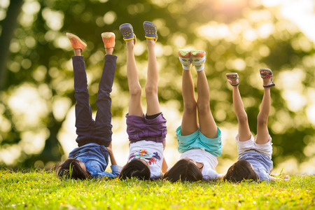 Group of happy children lying on green grass outdoors in spring park