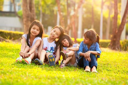 enfants qui jouent: Quatre sourire heureux enfant qui joue dans le parc, portrait en plein air