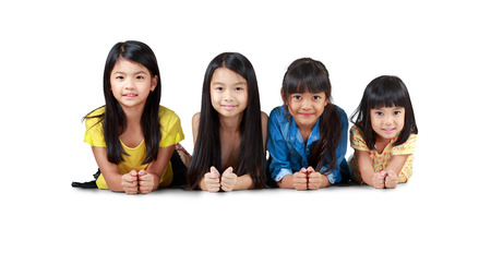 Four happy little asian girls laying on the floor, Isolated over white photo