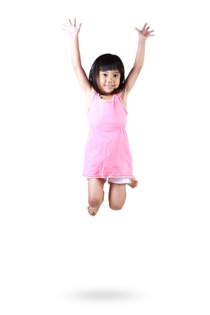 Adorable and happy little asian girl jumping in air, Isolated over white photo
