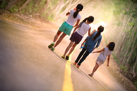 asian trees: four little asian girl walking on the road back to camera Stock Photo