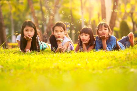 Leuke kinderen met bubble plezier op groen grasveld in het park