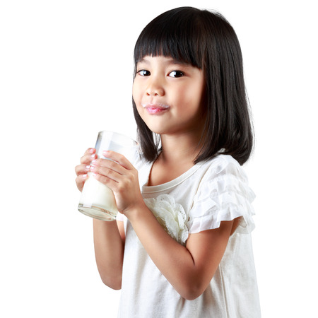 drinking milk: Happy little asian girl holding a cup of milk, Isolated over white