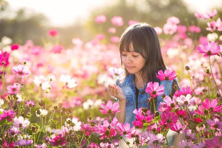 Weinig Aziatisch meisje in de kosmos bloem velden